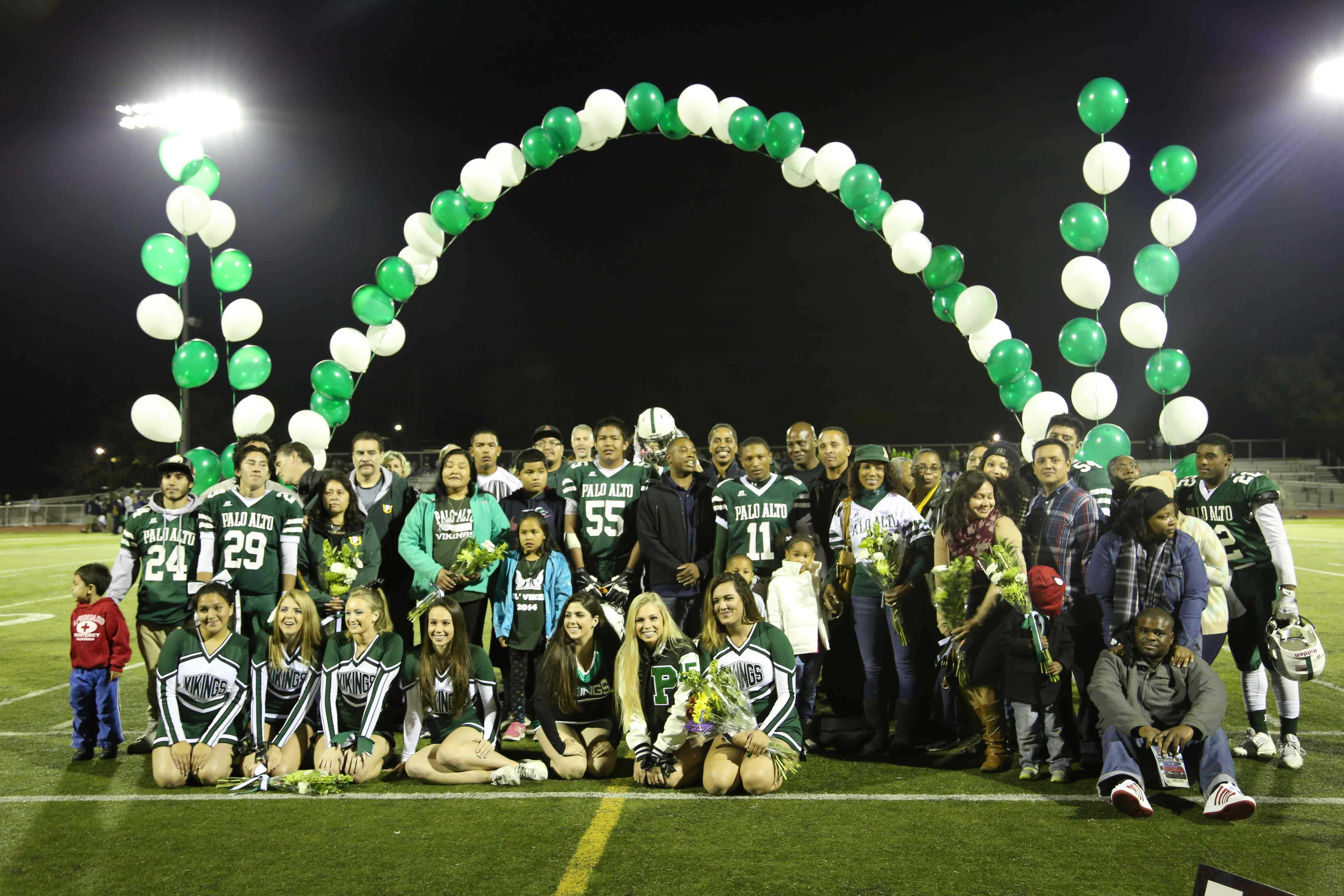 The six senior football players, six cheer and dance seniors, and their families pose for pictures in honor of their four years of commitment to Paly.