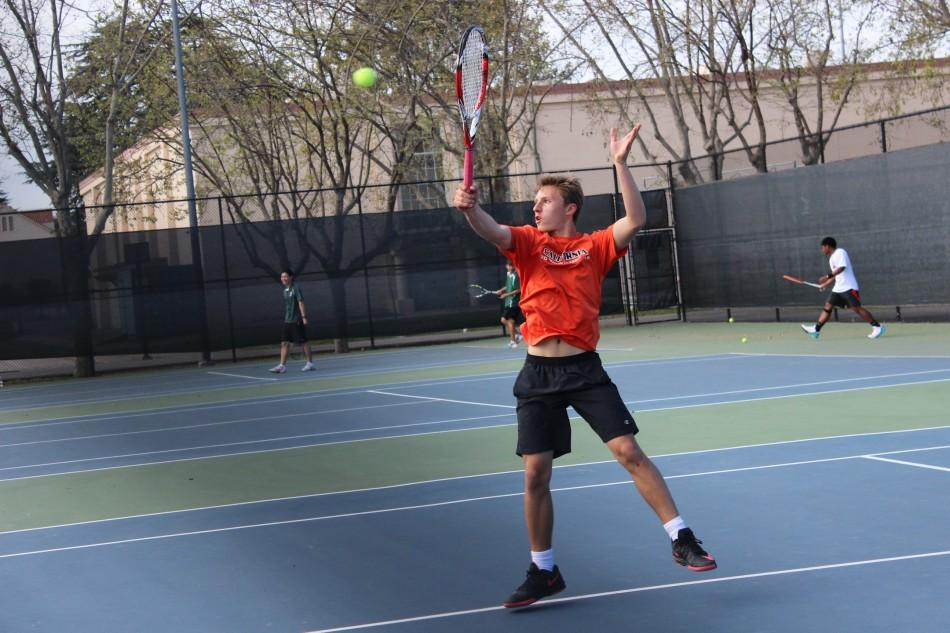 Carl+GoodFriend+%28%2716%29+jumps+up+to+serve+the+ball.+Paly+ended+up+winning+the+match+against+Aragon+High+School.