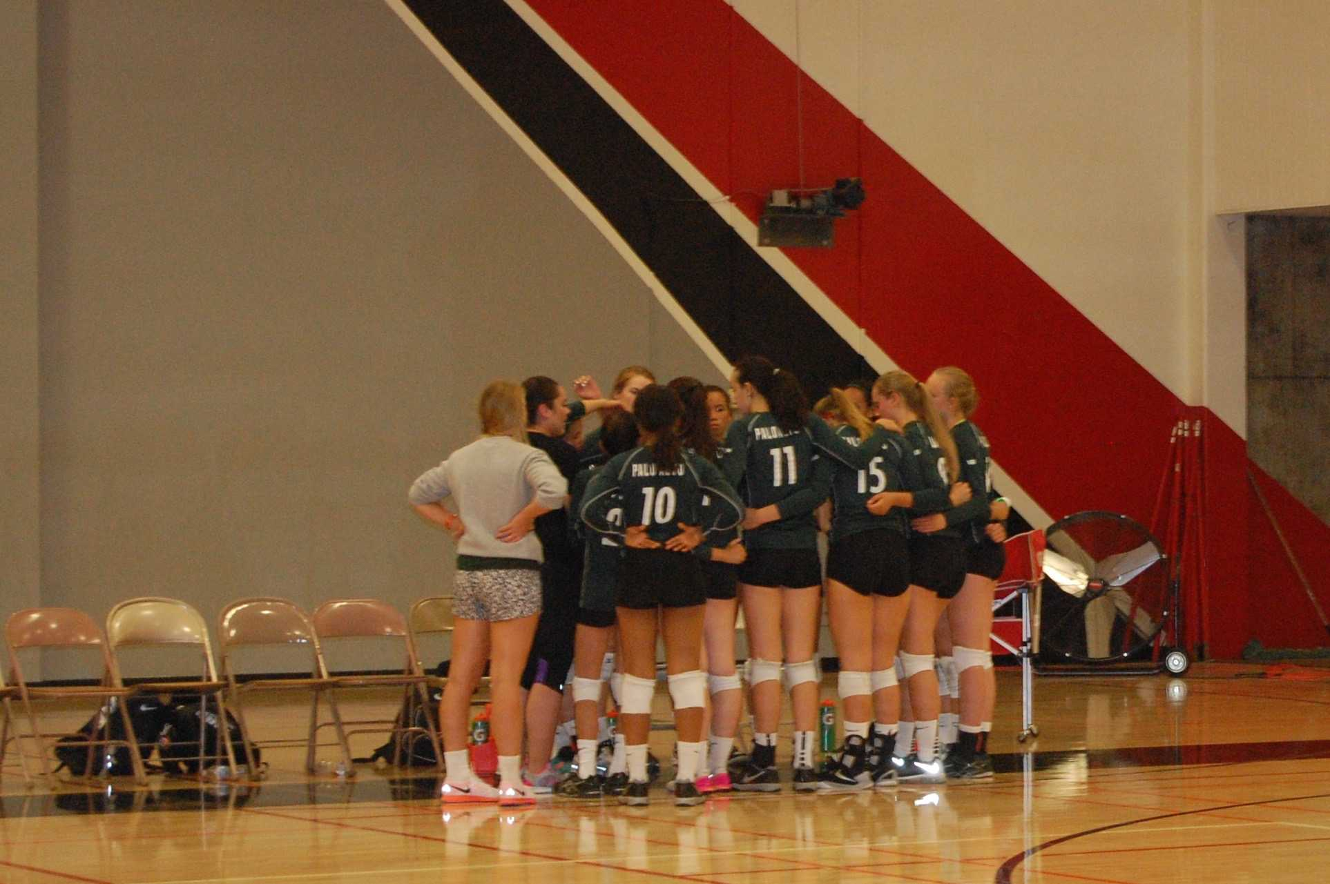 The volleyball team huddles during a timeout in their match against Woodside. The Vikings went on to win in three sets, 25-17, 25-16, 25-15.