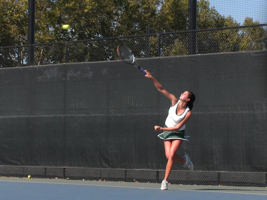 Sammy Solomon (14) rebounds from a serve while warming up before one of her matches.