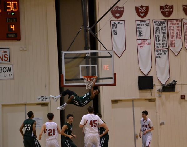 E.J. Floreal ('13) hangs off the hoop after dunking the ball. Floreal had 4 dunks on the night.