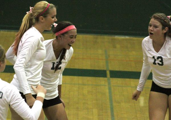 Jade Schoenberger ('15) celebrates with teammates Lauren Kerr ('14) and Sophia Bono ('13) after a kill. The Lady Vikes won this match in three sets.
