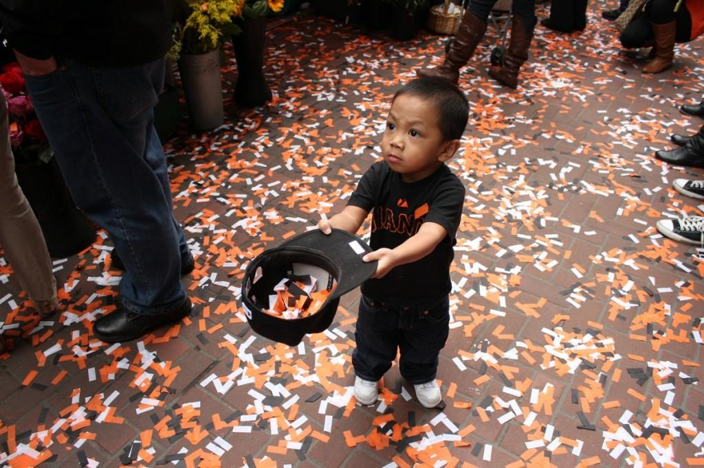 SAN FRANCISCO: Young Giants fan catches the magic in his hat along Market Street during the Giants parade yesterday. More than one million fans lined the streets of San Francisco to cheer on the World Series champions on Halloween.