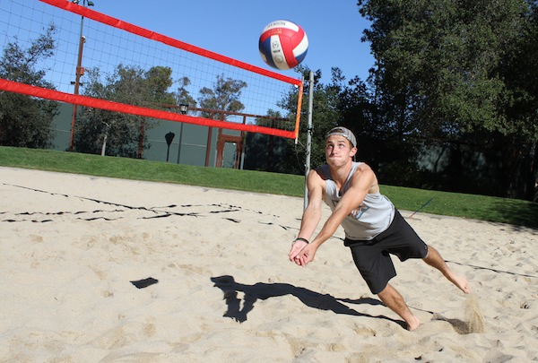 Josh Totte ('14) dives for a ball across the sand on a  warm, sunny Saturday afternoon.