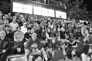 Parents and other fans sit on the bleachers to cheer on the competing players during the Paly Homecoming football game.