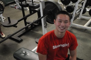Andrew Lau ('14) flashes a smile for the camera during his lifting workout in the Paly weightroom. Lau trains in the weightroom after school ends almost everyday for up to two hours.