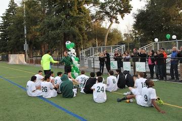 Goalkeeper Tony Maharaj ('14) shakes hands with Coach Don Briggs as Viking players and fans applaud. The Viking's would go on to win the game, 4-3.