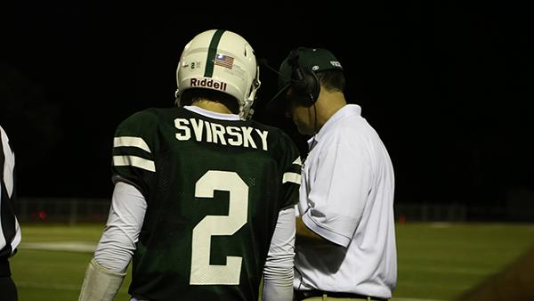 Svirsky and his coach discuss the next play in the game on the sideline.