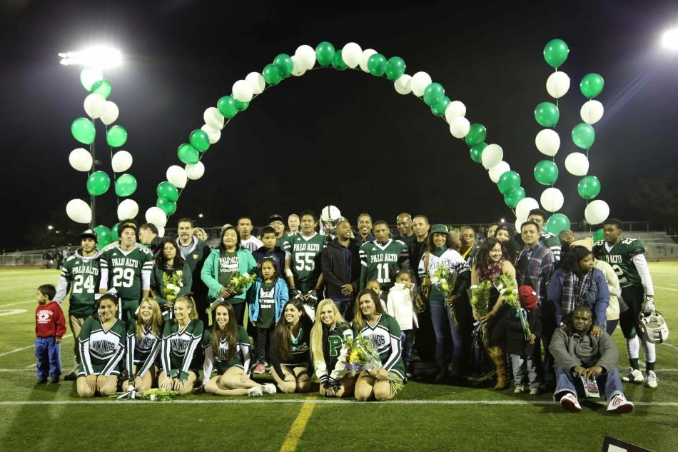 The+six+senior+football+players%2C+six+cheer+and+dance+seniors%2C+and+their+families+pose+for+pictures+in+honor+of+their+four+years+of+commitment+to+Paly.+