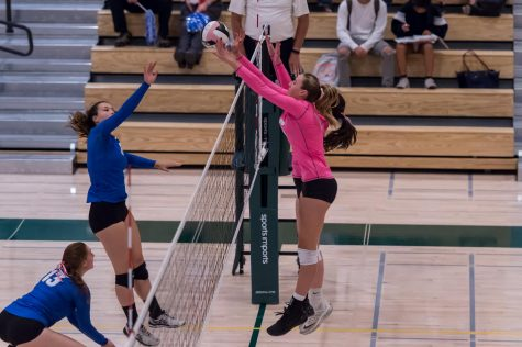 Amelia Gibbs ('18) and her teammate go up for a block.