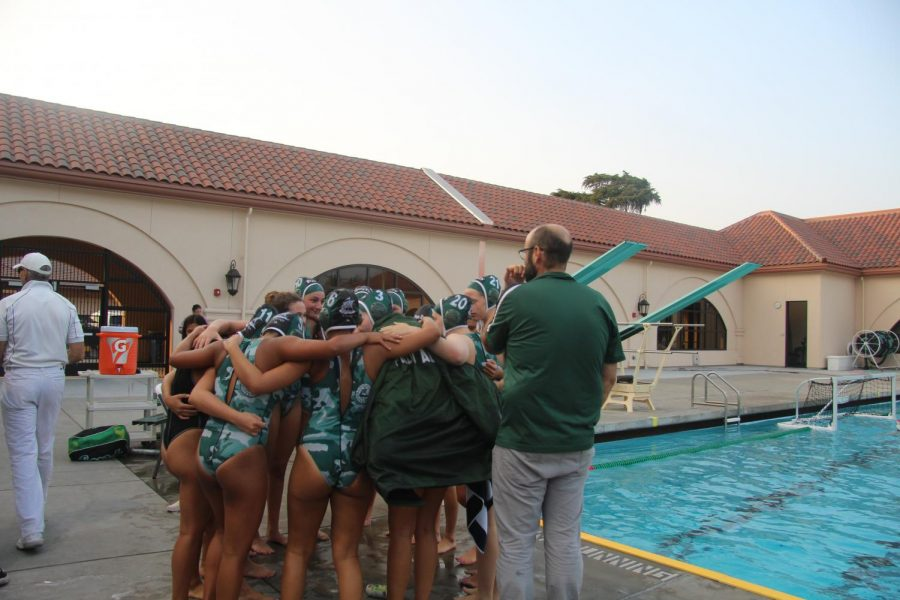 The girls water polo team stands in a huddle