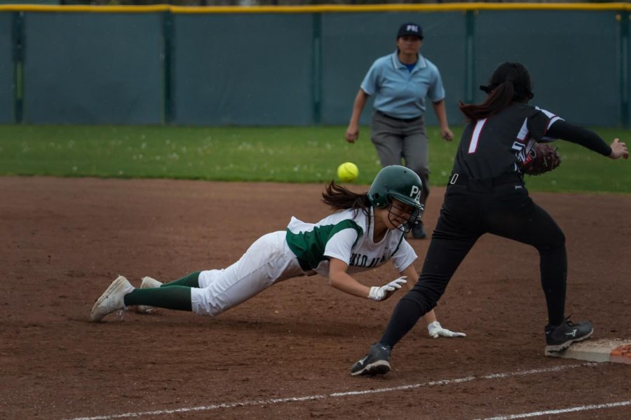 Lauren Chung (22') dives back to 1st base ahead of the ball.
