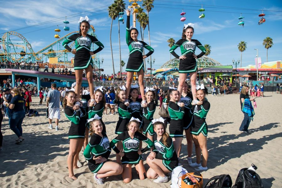 The cheer team stunts as they wait for awards to start.